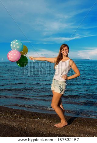Happy girl with balloons on sea background. Beach party decoration and red hair girl. Pretty woman holding air balloons casual photo. Summer holiday by seaside. Colorful air balloons in front of sea.
