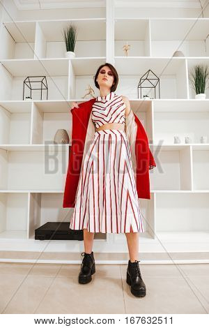 Beautiful young woman standing and taking off her red coat in the room