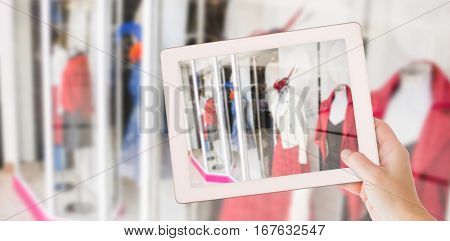 Masculine hand holding tablet against shops in shopping mall