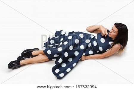Beautiful model laying on the white floor in studio with wwhite isolated background. She is looking aside and wearing long blue dress with polka dots and big black boots