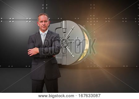 Serious manager with arms crossed in warehouse against digitally generated opened safe