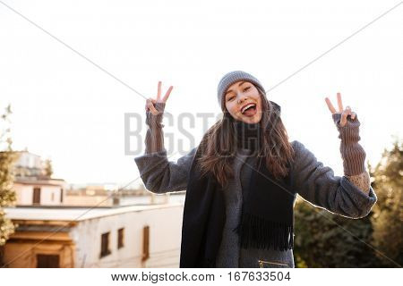 Cheerful young woman standing and showing peace sign in the city