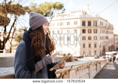 Smiling beautiful young woman with map and mobile phone standing in the city