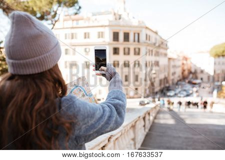 Back view of woman tourist taking pictures with blank screen smartphone in the city