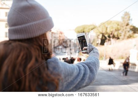 Back view of woman taking pictures with blank screen mobile phone in the city
