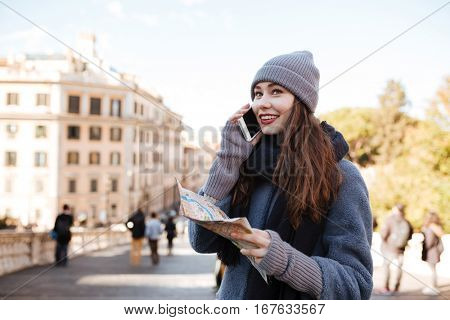 Cheerful beautiful young woman with map talking on mobile phone in the city