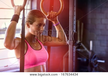 Young woman holding gymnastic rings while exercising in gym