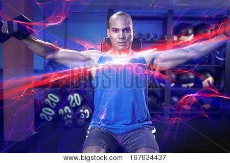 Portrait of determined male athlete exercising with dumbbells in fitness studio