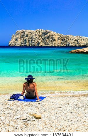 Girl on the  beautiful beach Kounoupa in Astypalea island, Greece