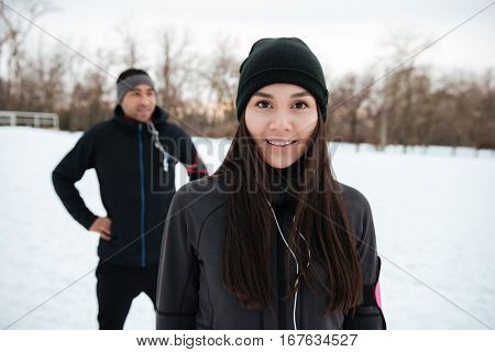 Close up portrait of a smiling young fitness girl looking at camera with african sportsman on the background outdoors in winter