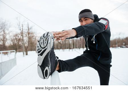 Portrait of an african fitness man stretching leg before running outdoors in winter