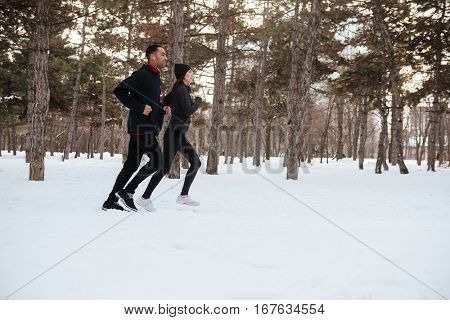 Healthy young couple jogging outside on snow in forest