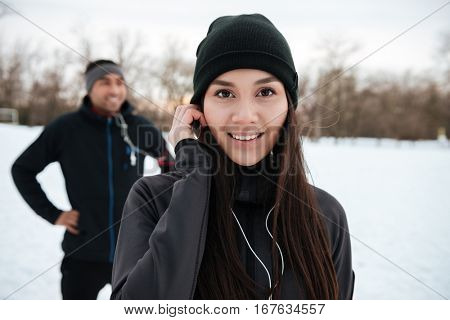 Close up portrait of a smiling lovely fitness girl looking at camera with african sportsman on the background outdoors in winter