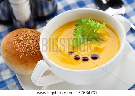 Bowl of delicious pumpkin soup on a table