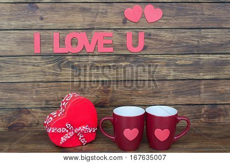 inscription I love you two flat pink heart box in the form of heart and two claret cup on a wooden background