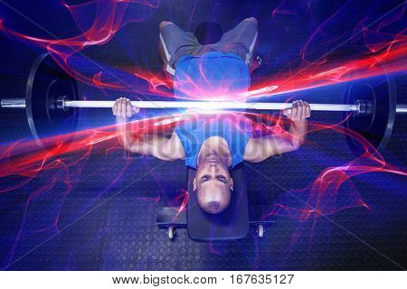 High angle view of man doing bench press with barbell in fitness studio