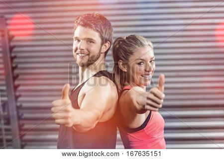 Portrait of serious couple standing back to back with thumbs up at gym