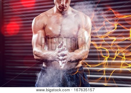 Shirtless man clapping hands with talc at  gym