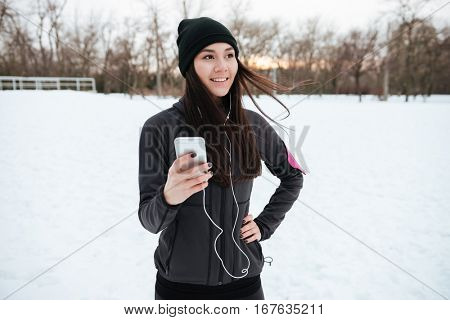 Smiling young sportswoman listening to music and jogging in the forest in winter
