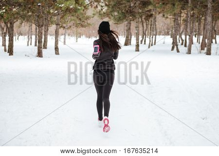 Back view of young fitness woman running in a city park in winter