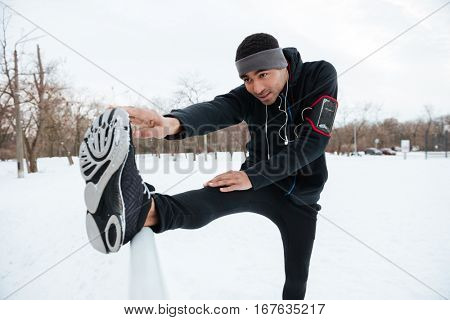 Portrait of an african fitness man stretching legs before running outdoors in winter