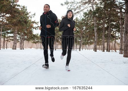 Portrait of an athlete man and woman running in the snow in the woods