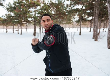 Young afro american jogger warming up before running outdoors in winter