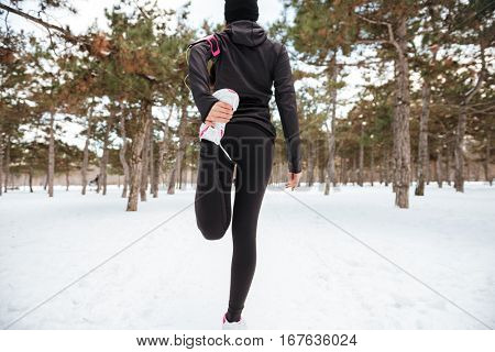 Back view of a fitness young woman stretching her legs outdoors in winter forest