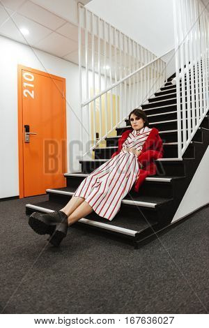 Relaxed stylish young woman in red coat lying on stairs in corridor