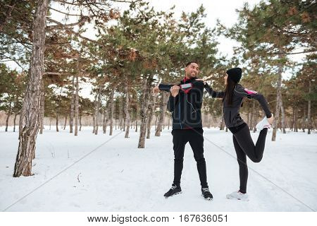 Couple enjoying time together while exercising outdoors in the winter forest