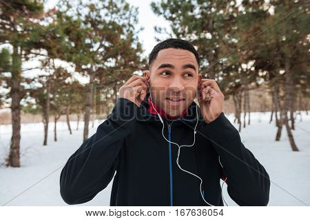 Portrait of a young african jogger with earphones listening music outdoors in winter
