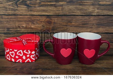 two claret cup and a box in the shape of a heart on a wooden background close up