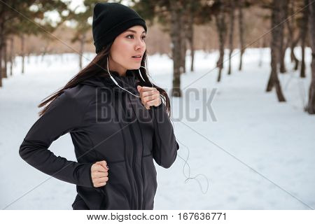 Close up portrait of a woman wearing sportswear running on snow with trees in background