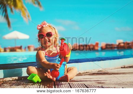 cute little girl playing on tropical beach, family at beach