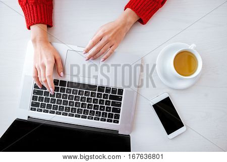 Top view photo of young lady sitting in cafe at cold winter day near phone and cup of tea while using laptop.