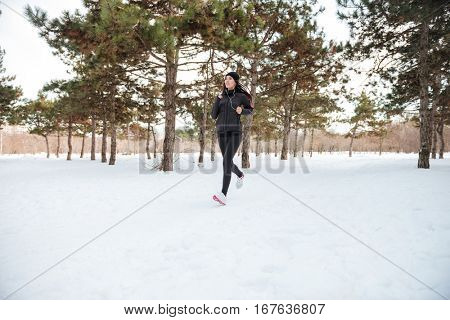 Beautiful young woman running jogging in the winter forest