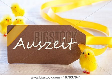 Label With German Text Auszeit Means Downtime. Easter Decoration Like Chicks. White Wooden Background. Card For Seasons Greetings