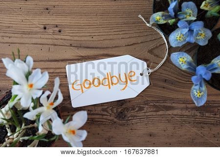 Label With English Text Goodbye. Spring Flowers Like Grape Hyacinth And Crocus. Aged Wooden Background