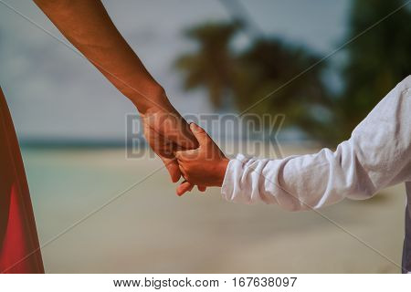 family protection -mother and son holding hands on beach