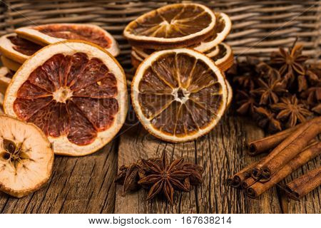 Star anise cinnamon apple oranges and grapefruit on the old wooden table. Selective focus.