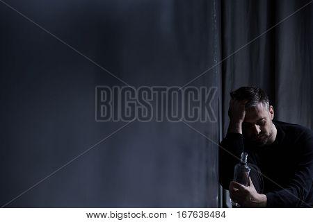 Man Staring At Alcohol Bottle