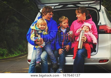 happy family with tree little kids travel by car on road