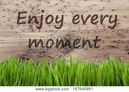 English Quote Enjoy Every Moment. Spring Season Greeting Card. Bright Aged Wooden Background With Gras.