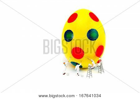 Miniature figurines painters painting yellow easter egg isolated on white background