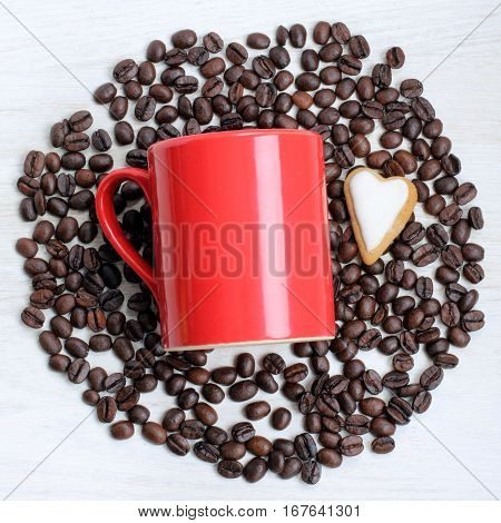 cookies in the shape of a heart and a red circle on the background of coffee beans top view / flavor favorite beverage