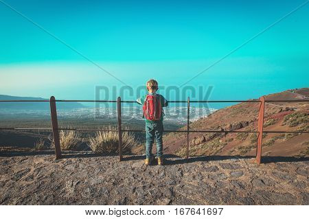 little boy looking at beautiful view while travel in mountains, travel concept
