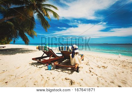 Two beach chairs on tropical vacation, family at beach