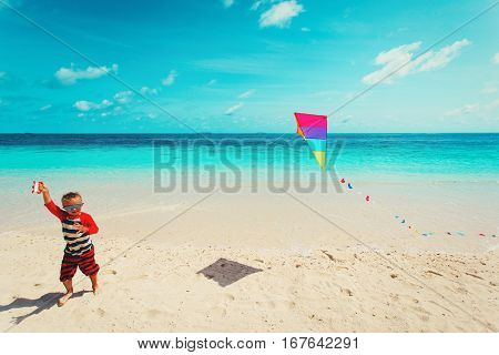 Little boy flying a kite on tropical beach, beach activities