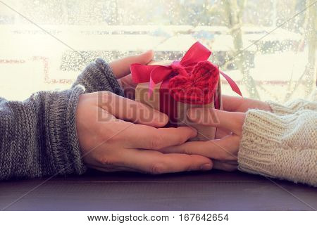 couple holds in hands gift with a heart symbol against the window / holiday greeting with a hint