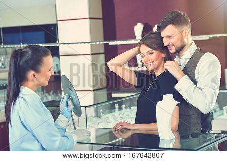 Couple of brunette woman, wearing black dress estimating looking at mirror. Handsome man trying necklace for his gorgeous wife at jewelry store. Jeweler in gloves holding mirror for buyer.